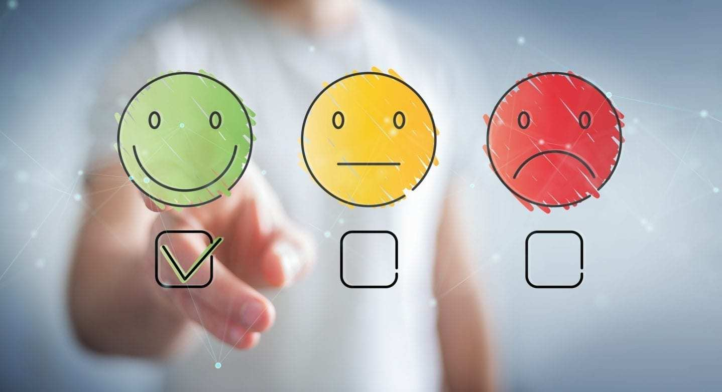 illustrations of smiley face, straight face, and frowning face in front of blurred figure selecting the smiley face