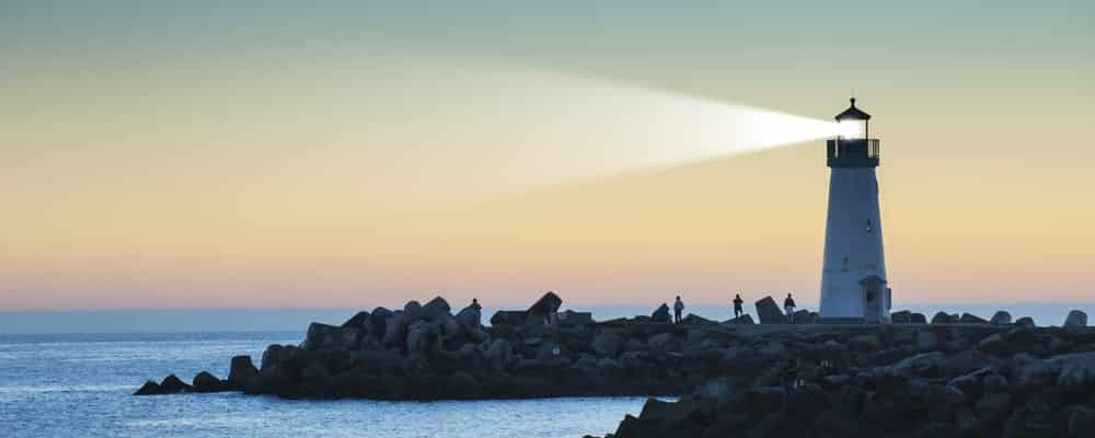 Lighthouse-emitting-beam-of-light-at-sunset